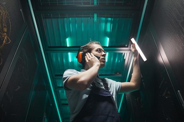 Retrato de ángulo bajo de ingeniero de red masculino hablando por teléfono inteligente en la sala de servidores mientras trabaja en el centro de datos, espacio de copia