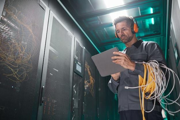 Retrato de ángulo bajo de ingeniero de red con tableta en la sala de servidores durante el trabajo de mantenimiento en el centro de datos, espacio de copia