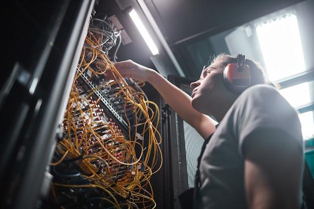 Retrato de ángulo bajo del ingeniero de redes conectando cables en la sala de servidores durante los trabajos de mantenimiento en el centro de datos, espacio de copia