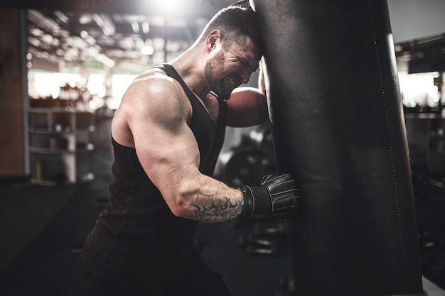 Retrato de ángulo bajo de joven deportista cansado apoyándose en saco de boxeo