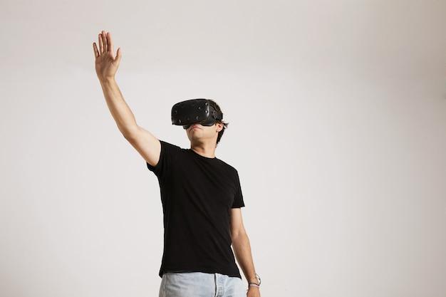 Retrato de ángulo bajo de una joven modelo caucásica en jeans y camiseta negra sin etiqueta extendiendo su mano mientras jugaba con gafas de realidad virtual en la pared blanca.