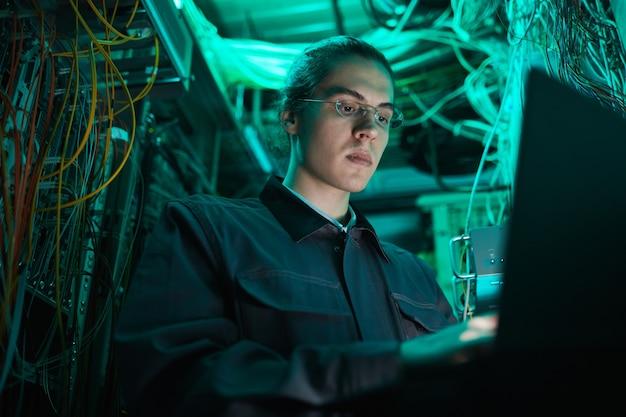 Retrato de ángulo bajo de joven técnico de red usando una computadora portátil en la sala de servidores mientras configura la supercomputadora en el centro de datos