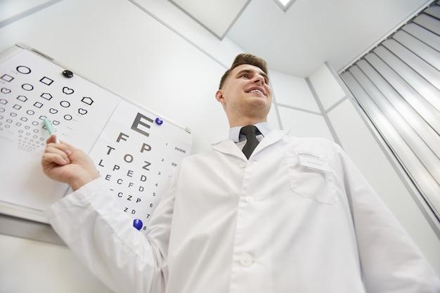 Retrato de ángulo bajo del oftalmólogo joven sonriente apuntando a la tabla de visión