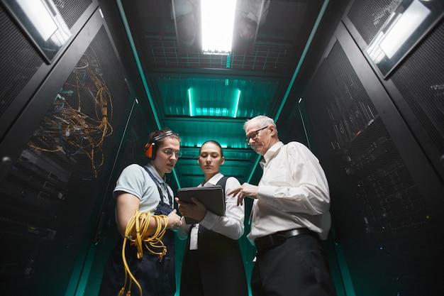 Retrato de ángulo bajo de personas que usan tableta en la sala de servidores mientras realizan trabajos de mantenimiento en el centro de datos, espacio de copia