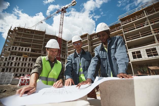 Retrato de ángulo bajo de tres trabajadores discutiendo planos de planta en el espacio de copia del sitio de construcción