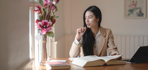 Retrato de una apasionada empresaria trabajando en su proyecto mientras mira por las ventanas, piensa y analiza los conceptos.