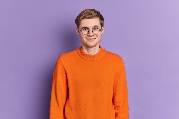 Retrato de un apuesto estudiante europeo tiene una sonrisa suave en la cara feliz de escuchar agradables puestos de noticias encantado lleva gafas redondas jersey naranja