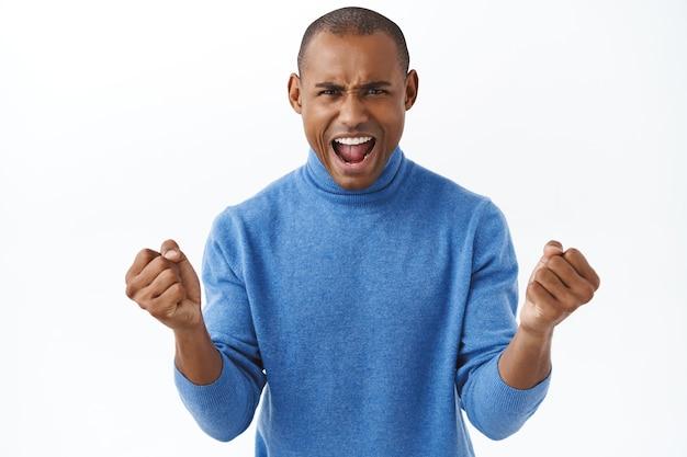 Retrato de un apuesto hombre afroamericano entusiasta y fuerte, gritando para aumentar la confianza, viendo la transmisión en vivo de televisión en línea del juego deportivo