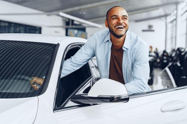 Retrato de un apuesto hombre afroamericano feliz cerca de su coche nuevo