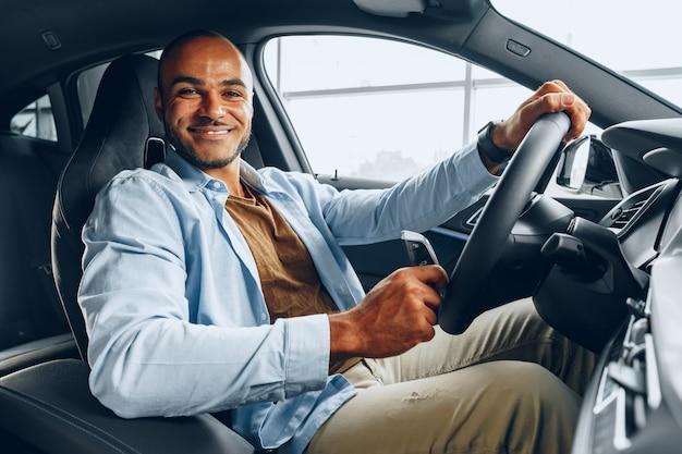 Retrato de un apuesto hombre afroamericano feliz sentado en coche nuevo