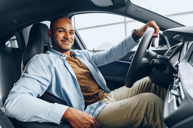 Retrato de un apuesto hombre afroamericano feliz sentado en su coche recién comprado de cerca