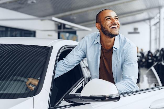Retrato de un apuesto hombre afroamericano feliz sentado en su coche recién comprado