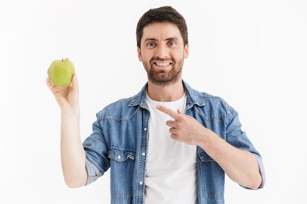 Retrato de un apuesto hombre barbudo con ropa casual que se encuentran aisladas, mostrando manzana verde, apuntando