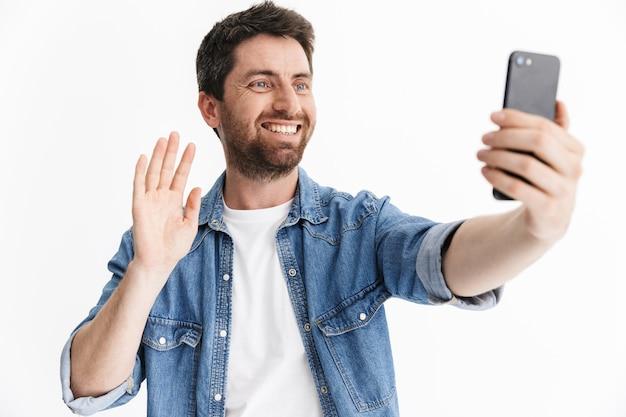 Retrato de un apuesto hombre barbudo con ropa casual que se encuentran aisladas, tomando un selfie