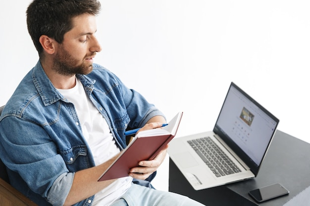 Retrato de un apuesto hombre barbudo con ropa casual sentado en una silla aislada sobre una pared blanca, trabajando en una computadora portátil