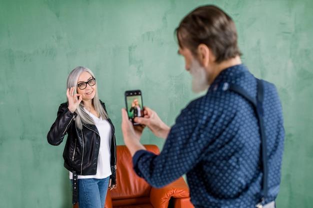 Retrato del apuesto hombre barbudo senior tomando fotos de su bella mujer, posando para la cámara sobre fondo verde de la pared y mostrando gesto bien ok