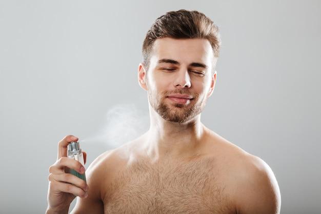 Retrato de un apuesto hombre medio desnudo rociando perfume