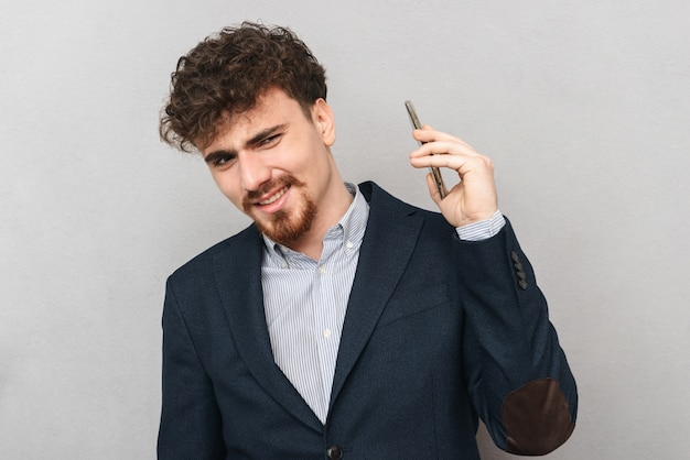 Retrato de un apuesto hombre de negocios joven confuso disgustado aislado sobre pared gris hablando por teléfono móvil.