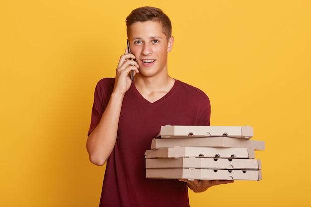 Retrato de un apuesto joven adolescente rubio con teléfono inteligente y cajas con comida, trayendo orden, llamando a un cliente