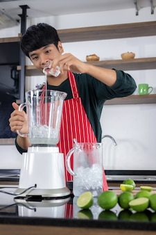 Retrato de un apuesto joven de asia con una sonrisa feliz y vistiendo un delantal rojo en una cocina moderna.
