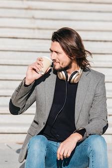 Retrato de un apuesto joven con auriculares alrededor de su cuello tomando café para llevar
