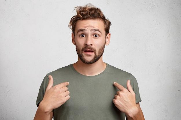 Retrato de apuesto joven barbudo señala a sí mismo desconcertado por ser elegido