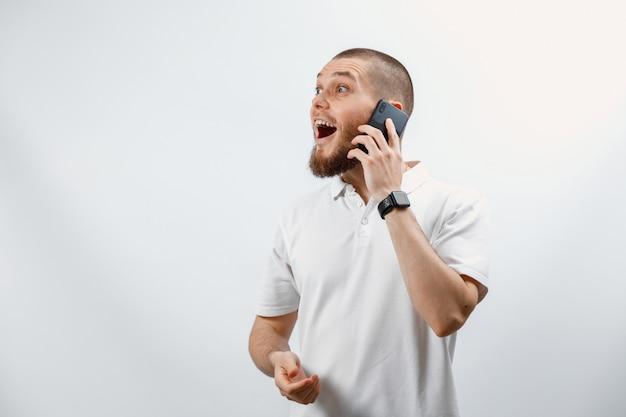 Retrato de un apuesto joven en una camiseta blanca hablando por teléfono inteligente en blanco
