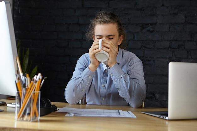 Retrato de un apuesto joven empleado sentado en su escritorio de oficina con papeles y aparatos electrónicos modernos, sosteniendo una taza y bebiendo café o té recién hecho mientras se siente somnoliento o cansado