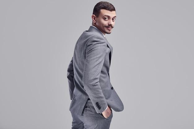 Retrato de apuesto joven empresario árabe confiado con elegante bigote en traje gris de moda mira por encima del hombro en el estudio