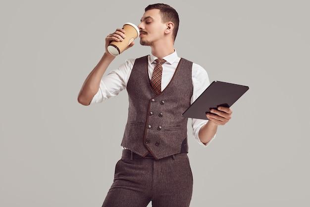 Retrato de apuesto joven empresario árabe confiado con elegante bigote en traje marrón de lana tiene tableta y tomar café en estudio
