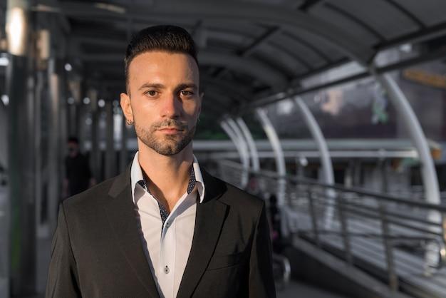 Retrato de apuesto joven empresario italiano al aire libre en la ciudad vistiendo traje
