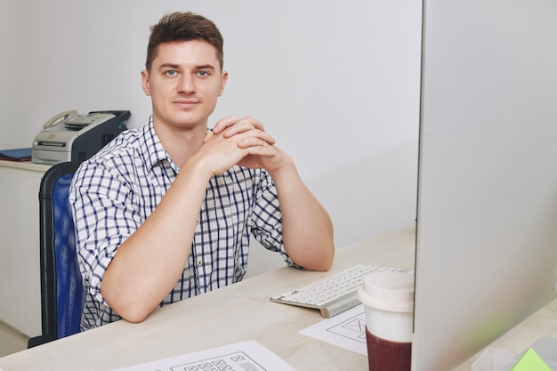 Retrato de apuesto joven empresario sonriente sentado en el escritorio de oficina y mirando al frente