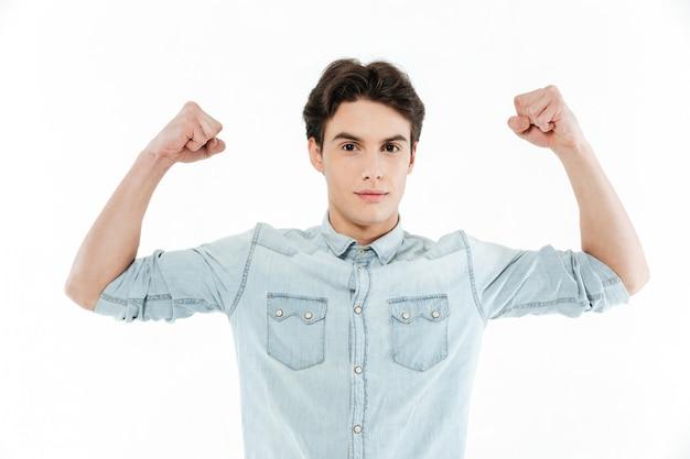 Retrato de un apuesto joven flexionando los músculos bíceps