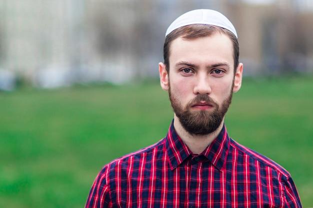 Retrato de apuesto joven judío en tocado masculino judío tradicional, sombrero, boom o yiddish en la cabeza. hombre serio de israel con barba al aire libre. copia espacio, lugar para texto.