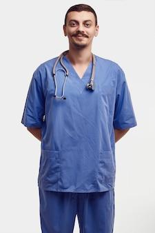 Retrato de apuesto joven médico árabe confiado con bigote elegante en azul aislado en blanco