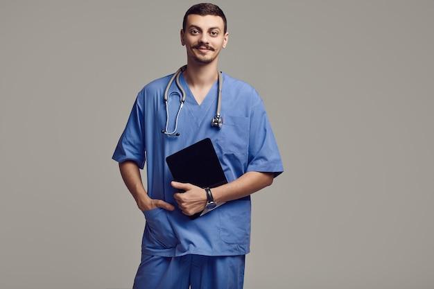 Retrato de apuesto joven médico árabe confiado con bigote elegante en azul tiene tableta en estudio gris
