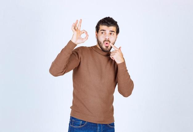 Retrato de un apuesto joven mostrando gesto bien aislado sobre fondo blanco. foto de alta calidad