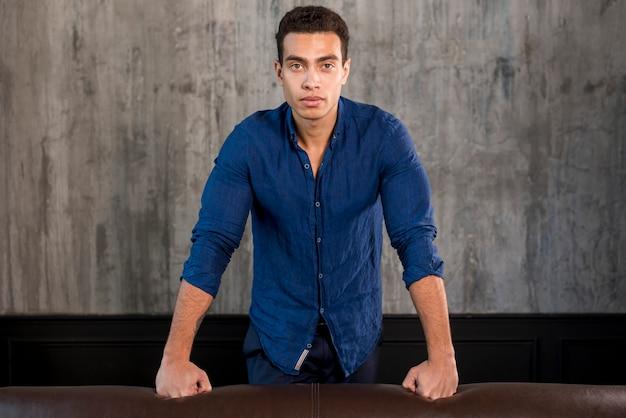 Retrato de un apuesto joven parado detrás del sofá contra una pared gris de concreto