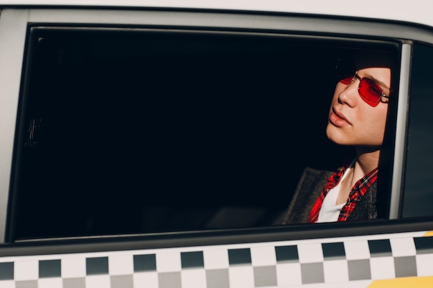 Retrato de un apuesto joven viajando en el asiento trasero de un taxi