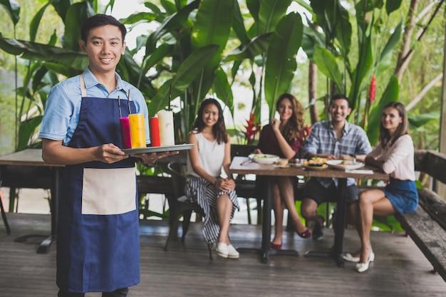 Retrato de apuestos camareros listos para servir las bebidas a sus clientes