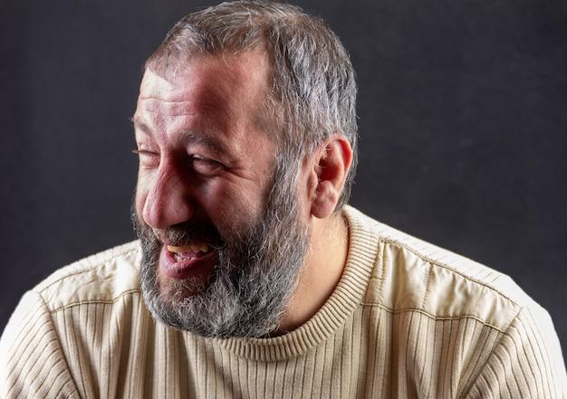 Retrato de un armenio barbudo gris sonriente sobre un gris oscuro