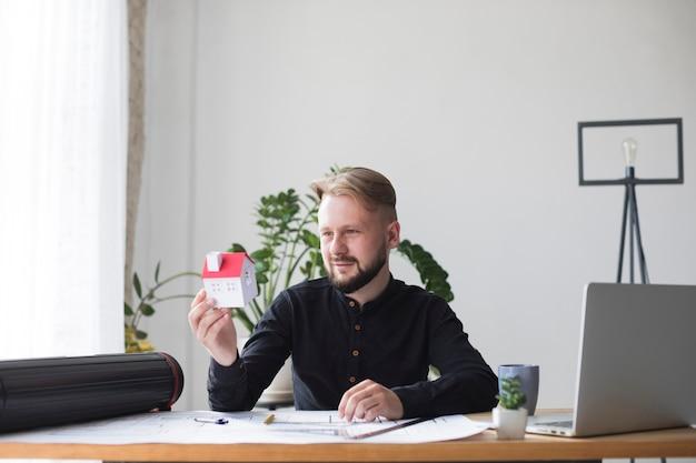 Retrato de una arquitectura masculina joven que sostiene el modelo de la casa mientras que se sienta en oficina