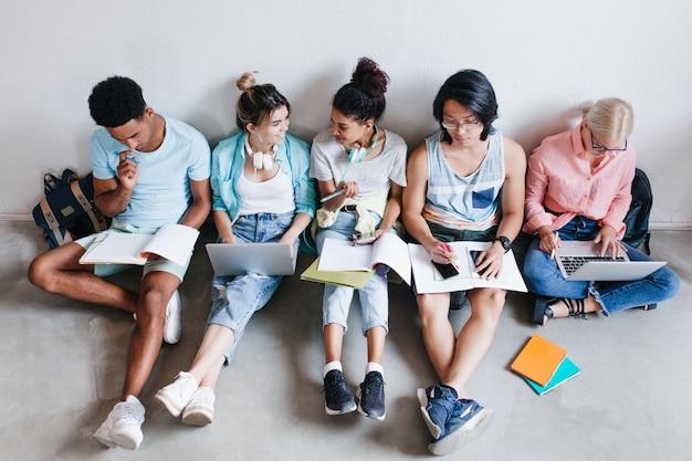Retrato de arriba de estudiantes internacionales esperando la prueba en la universidad. grupo de compañeros de universidad sentados en el suelo con libros y portátiles, haciendo los deberes.
