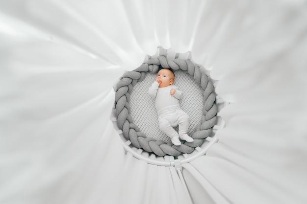 Retrato desde arriba del hermoso bebé recién nacido acostado boca arriba en cama redonda blanca con dosel.