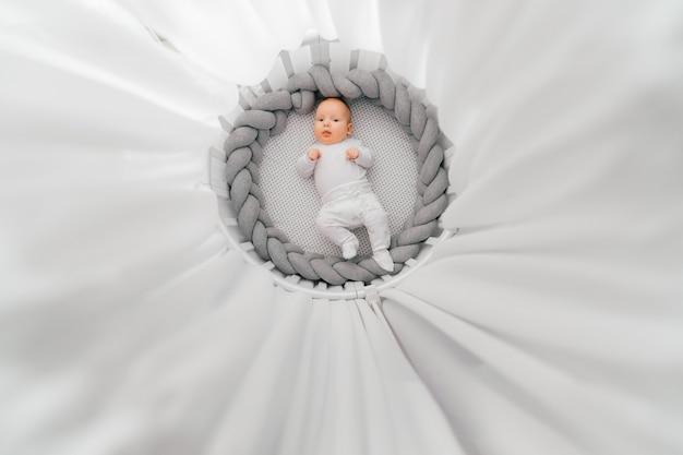 Retrato desde arriba del hermoso bebé recién nacido acostado sobre la espalda en la cama redonda blanca con dosel.