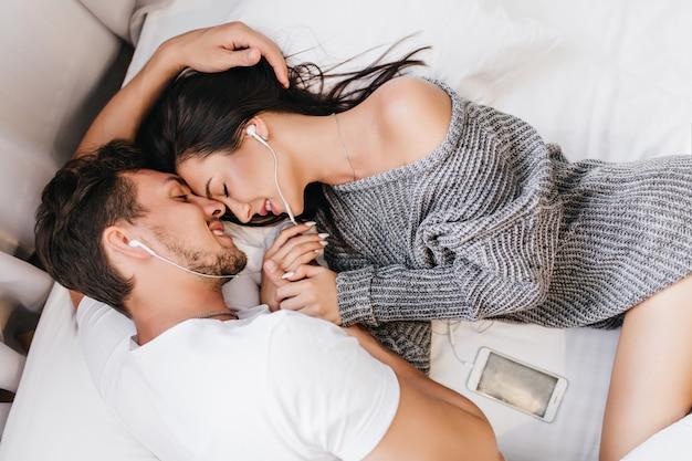 Retrato de arriba de morena hombre acostado en la cama con su novia