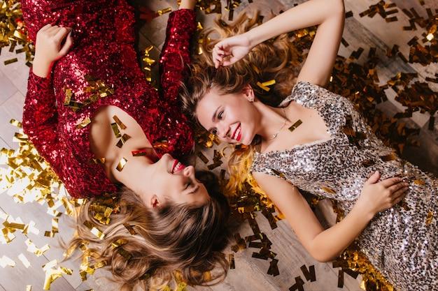 Retrato de arriba de mujeres inspiradas viste atuendos brillantes con una linda sonrisa, mientras descansa después de la fiesta de año nuevo