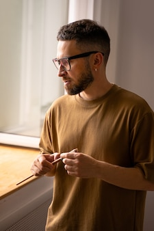 Retrato de artista masculino de pie mirando por la ventana en busca de inspiración coaching en pintura