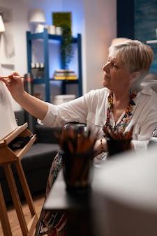 Retrato de artista senior sentado en silla de ruedas en el estudio