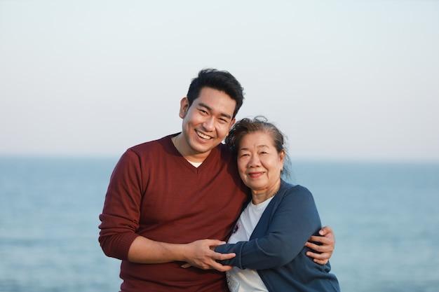 Retrato de asia madre senior y joven hijo sonrisa y cara feliz